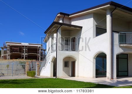 New Two-story House With Garden, Balcony And Stairs To The Right And Unfinished Building