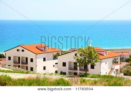 Building Of New Two-storey White Houses With Brown Roofs And Balcony On Coast