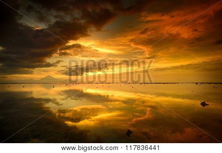 Beautiful orange sunset over the island of Bali Agung volcano on the background.