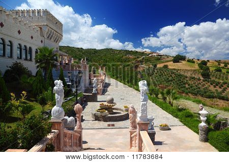 Botanic Garden With Sculptures, Benches And Fountain Near Ancient White Castle On Hill
