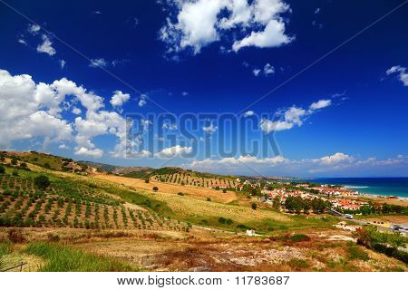 Big Clearing With Green Bushes, Trees And Houses On Coast Under Big Blue Sky