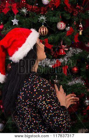 Back Of Woman Wishing At Christmas Tree