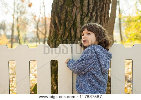 Toddler Boy Standing Near  White Fence