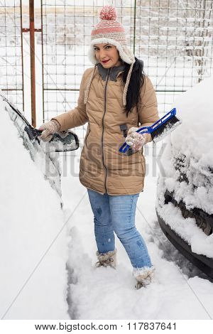 Woman Cleaning Snow From Car