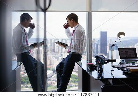 Business Person With Coffe Cup Reading News On Tablet