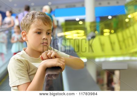 Little Serious Boy Standing On Escalator And Moving Up, Looking At Side