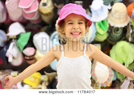 Portrait Of Little Girl Trying Pink Panama In Store And Smiling, Counter With Commodity