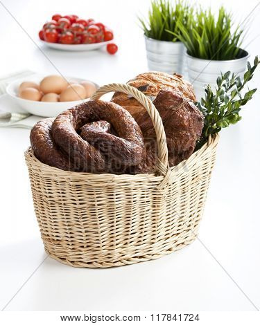 Various cold meats in wicker easter basket