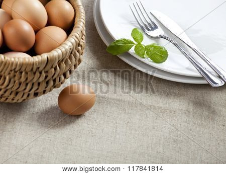 Easter table. Basket with eggs, white plates with silver cuttle ry