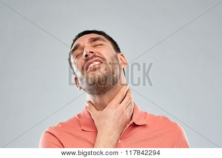 people, healthcare and problem concept - unhappy man touching his neck and suffering from throat pain over gray background