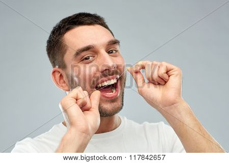 health care, dental hygiene, people and beauty concept - smiling young man with floss cleaning teeth over gray background