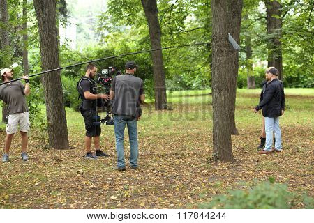 RUSSIA, MOSCOW - 30 JUL, 2015: Five men are standing in the Sokolniki park and shooting movie (Maximum shock).