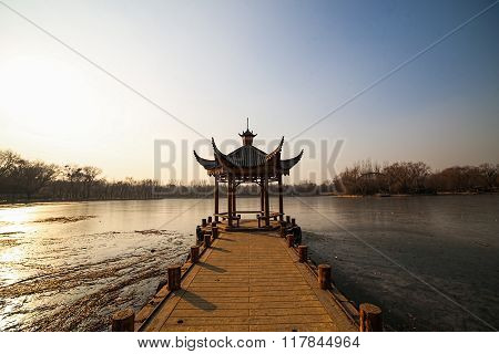Beautiful Chinese gazebo in the middle of a frozen lake in the park on a background of trees.