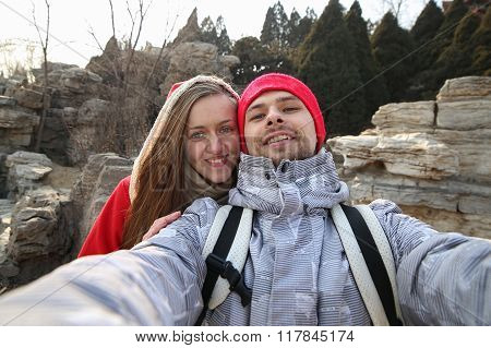 Beautiful happy couple makes selfie on a background of mountains in the park