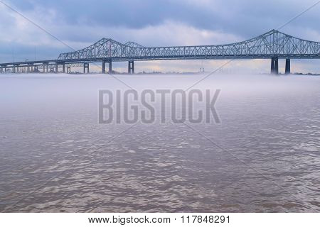 Crescent City Connection Bridge on the Mississippi River with a layer of fog over the water taken in New Orleans, LA