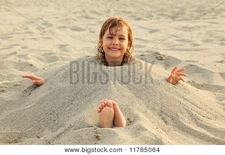 Little Girl After Swimming Is Buried In Sand On Beach, A Lot Of Yellow Sand