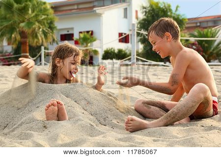 Little Brother And Sister Playing In Sand On Beach, Buildings And Palm Trees, Focus On Boy