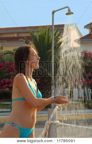 Young Beautiful Woman Wearing In Blue Bathing Suit Takes Shower