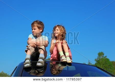 Little Boy And Girl Sitting On Car Roof On Blue Sky, Hands On Legs