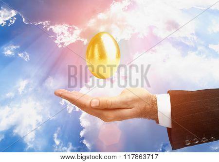 Golden Egg Over Male Hand