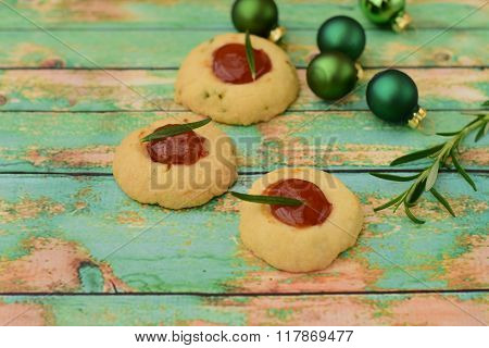 Rosemary thumbprint cookies with berry jam on green wood background