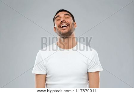 emotion and people concept - laughing man over gray background