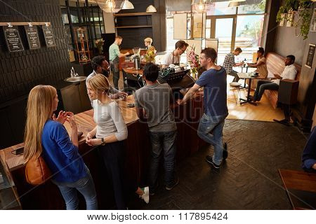 People waiting at a coffee shop counter for their orders