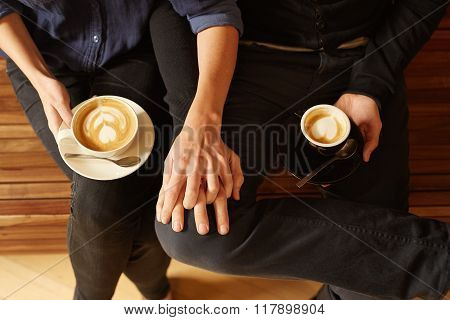 Overhead of a couple sitting close with coffee
