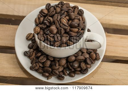 Coffee Beans In The Cup And On The Saucer.