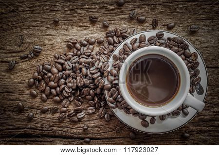 White Coffee Cup And Coffee Beans On Old Wooden Background. Top View .