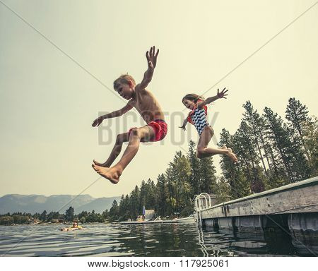 Kids jumping off the dock into a beautiful mountain lake. Having fun on a summer vacation at the lake with friends