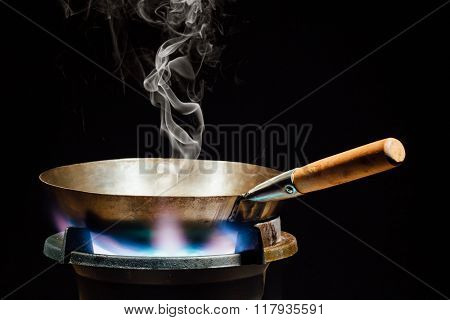 chinese wok pan on fire gas burner