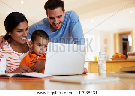 Family In Kitchen Looking At Laptop Together