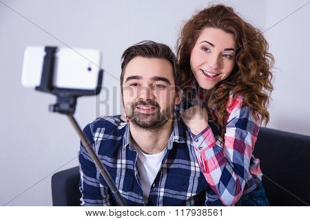 Young Beautiful Couple Taking Photo With Smart Phone On Selfie Stick