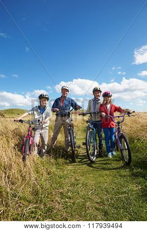 Grandparents With Children Cycling Through Countryside