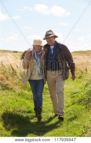 Senior Couple Walking In Countryside Together
