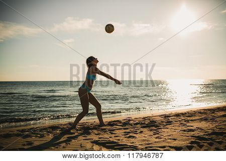 Young active woman playing volleyball on the beach with a partner.Playing beach summer sports on the sand at sunset.Living healthy active fitness lifestyle doing sport on beach