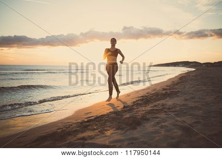 Runner woman jogging on beach in sportswear.Beautiful fit female fitness woman training and jogging
