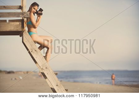 Happy woman photographer on vacation shooting.Photographer ready to take ocean pictures with dslr camera on the beach.Professional travel lifestyle photography.Summer memories.Capturing moment of life