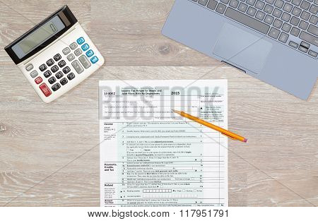 Laptop And Calculator On 2015 Irs Form 1040Ez