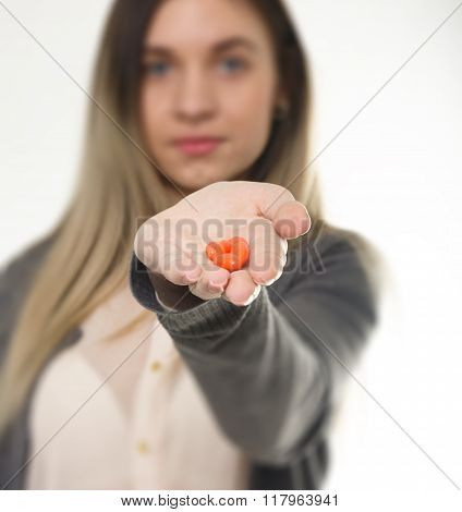 young woman holding the drugs at arm's length. she offers a taste of the tablets