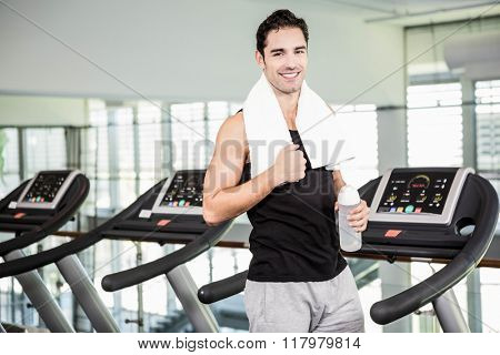 Smiling man on treadmill holding bottle of water at the gym