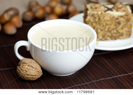 cup of cappuccino a piece of cake with nuts on a plate lying on a bamboo mat poster