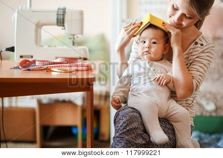 Raising children, child care, baby sitter. Mother and infant at home playing role-playing games. Cut