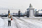 Girl holding a map at the Langelinie Gate in the park in winter Copenhagen. Langelinie is a pier promenade and park in central Copenhagen Denmark and home of the statue of The Little Mermaid. poster