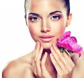 Beauty Portrait. Beautiful Spa Woman Touching her Face .  Cosmetics and cosmetology. Clean face , skin care .  girl with delicate flower near the face poster
