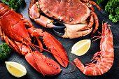 Fine selection of crustacean for dinner. Lobster crab and jumbo shrimp on dark background poster