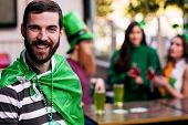 Portrait of man celebrating St Patricks day with friends poster
