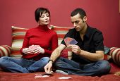 young couple having fun playing cards at home poster
