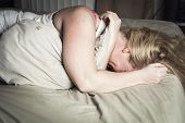A woman feel sick lying down on bed poster